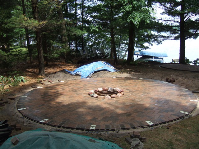 Lakeside Firepit (after) using pavers and stone with glow-in-the-dark paver stones spaced around edge for safety at night.