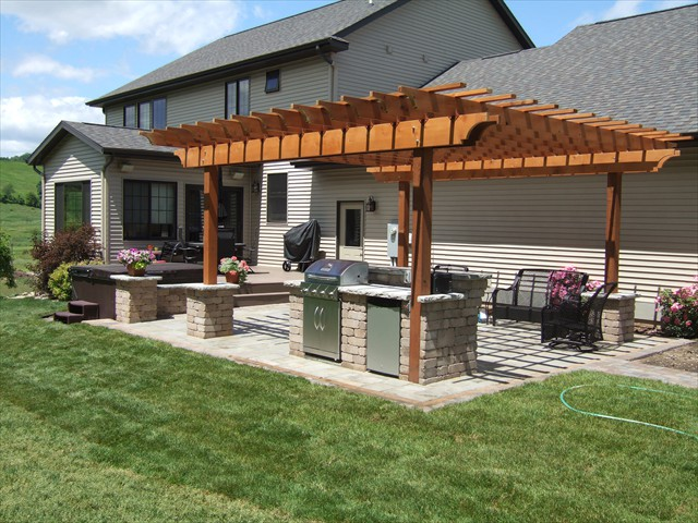 Backyard after installation of outdoor kitchen and pergola